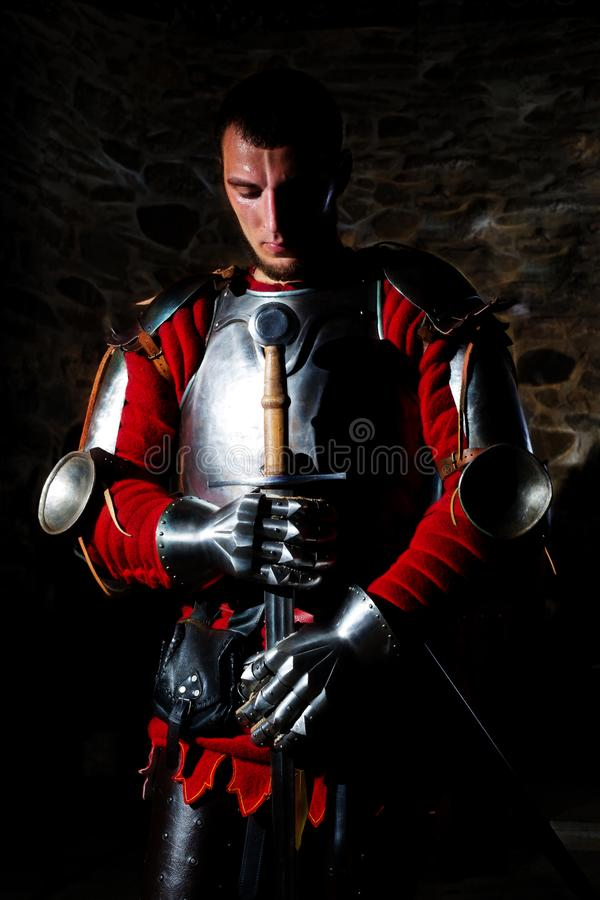 Knight Standing With Metal Sword And With Head Bowed In Prayer. Brave knight standing with metal sword, armor,gloves,hauberk and with head bowed in prayer stock images