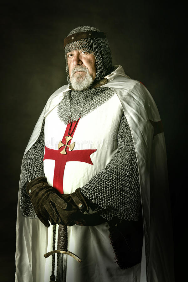 Knight Templar. Posing with sword in a dark background royalty free stock photos