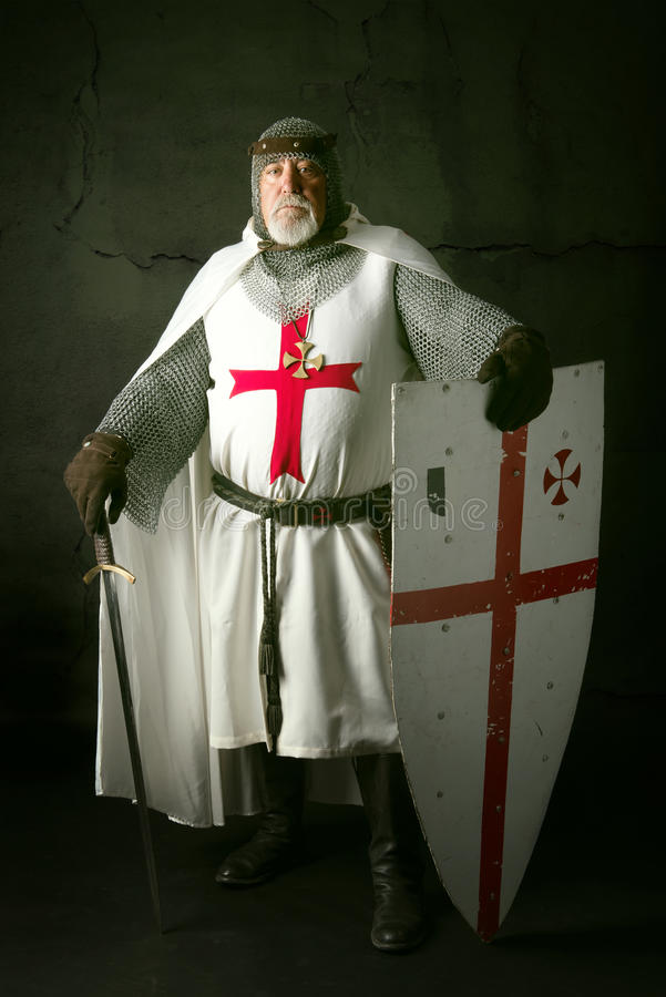Knight Templar. Posing with sword in a dark background royalty free stock photography