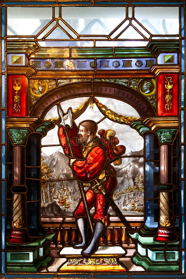 Knight with weapon in the colored stained glass of the interior of Peles Castle in Romania stock photo