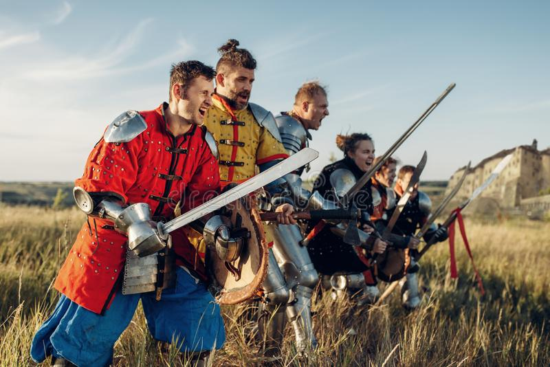 Knights in armor standing in a row before battle. Medieval knights in armor and helmets standing in a row before battle. Armored ancient warrior in armour posing royalty free stock image