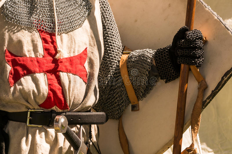 Knights templar. A close shot of persons torso dressed up historically to mimic a knights templar in full armour holding his helmet under the arm with his sword royalty free stock image