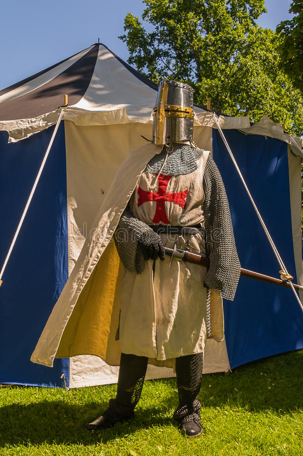 Knights templar. A person dressed up historically to mimic a knights templar in full armour standing in front of a white and blue tent stock photo