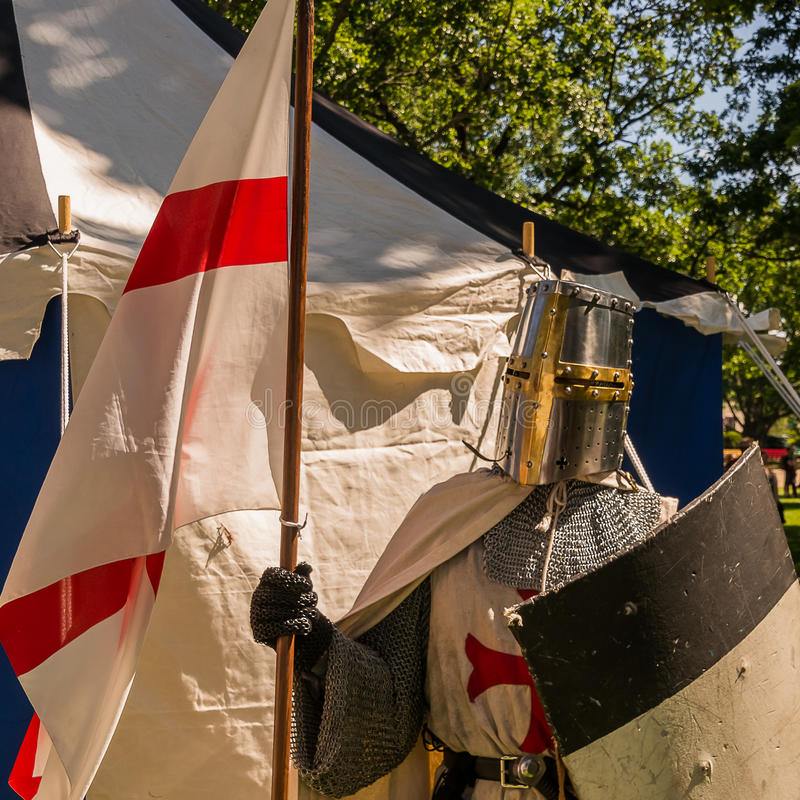 Knights templar. A person dresses up historically to mimic a knights templar in full armour standing in front of a white and blue tent holding a shield and flag royalty free stock photo