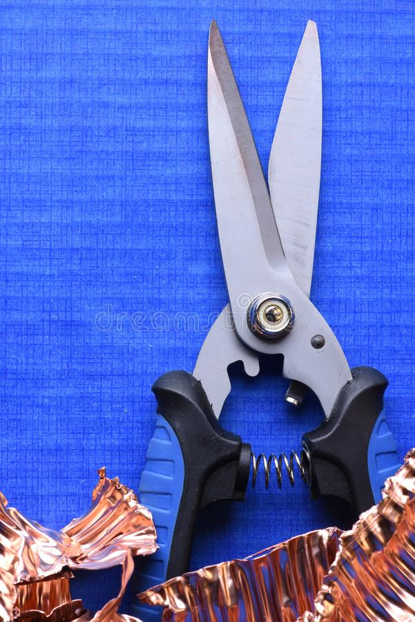 Knip Snijder en Koperschroot op blauwe achtergrond royalty-vrije stock afbeelding