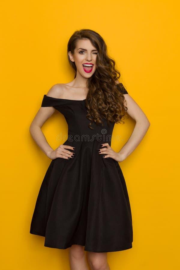 Knipogende Elegante Vrouw in Zwarte Kleding stock foto's