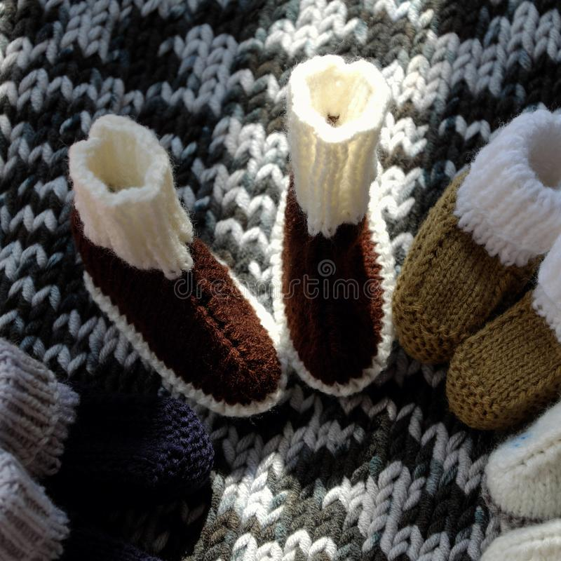 Knit baby booties. For newborn from yarn on woolen blanket, cute handmade products for footwear stock image