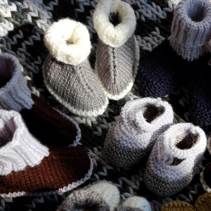 Knit baby booties. For newborn from yarn on woolen blanket, cute handmade products for footwear royalty free stock photos