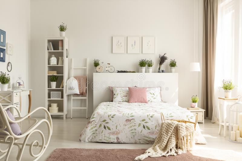 Knit blanket in basket standing on dirty pink carpet in real photo of bright feminine bedroom interior with stock photos