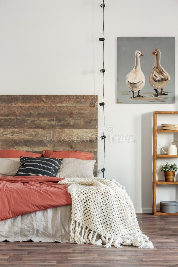 Free Knit Blanket On A Bed With Wooden Bedhead Standing Against White Wall With An Oil Painting Of Ducks. Real Photo Of Bedroom Stock Photo - 158306520