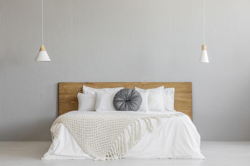 Knit blanket on wooden bed against grey wall in minimal bedroom royalty free stock photography