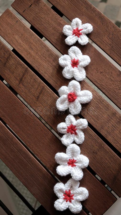 Knit daisy flower on wood background. Group of handmade product for mother day, white daisy flower on wood background, make by knit from yarn royalty free stock image