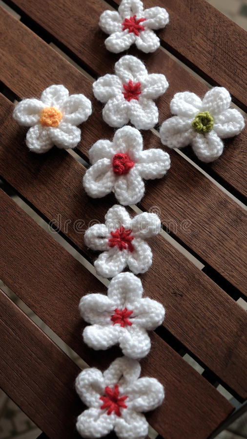 Knit daisy flower on wood background. Group of handmade product for mother day, white daisy flower on wood background, make by knit from yarn stock photo