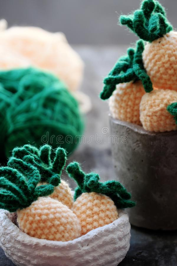 Knit handmade product, pineapples fruit on grey wooden background. Handmade product from knit on grey wooden background, group of pineapples fruit in yellow with stock photos