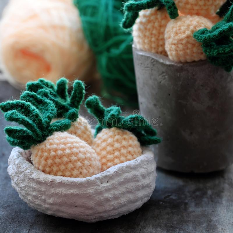 Knit handmade product, pineapples fruit on grey wooden background. Handmade product from knit on grey wooden background, group of pineapples fruit in yellow with royalty free stock photo