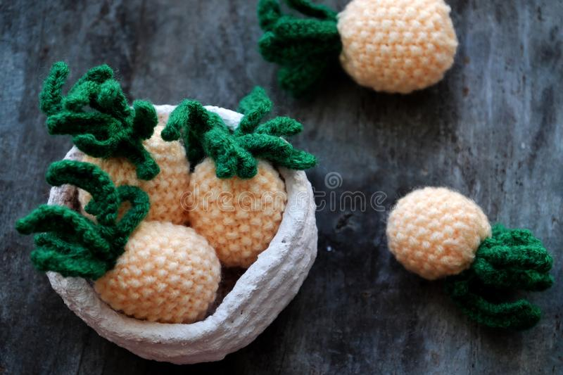 Knit handmade product, pineapples fruit on grey wooden background. Handmade product from knit on grey wooden background, group of pineapples fruit in yellow with stock photo