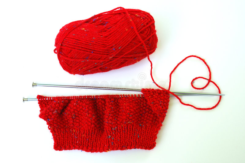 Knit red sweater with love. Knitting is a method by which thread or yarn may be turned into cloth. Knitting consists of loops called stitches pulled through stock photography