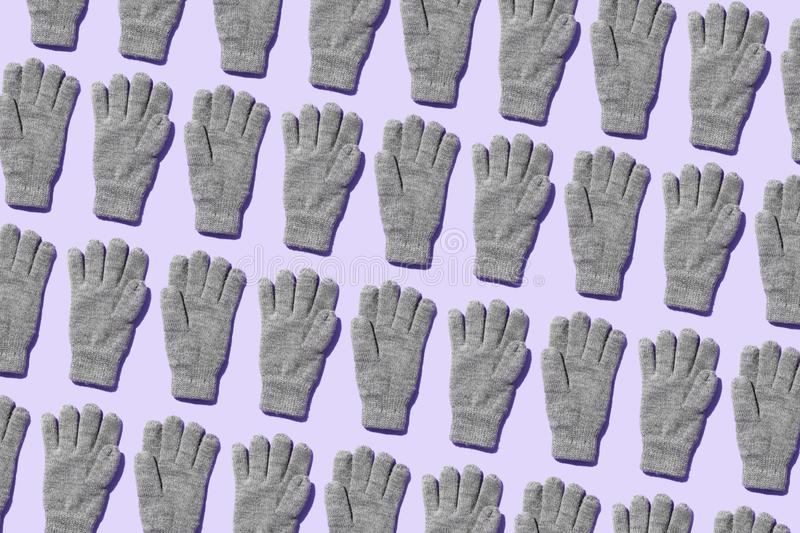 Knit winter gloves. Organized over purple background royalty free stock photography