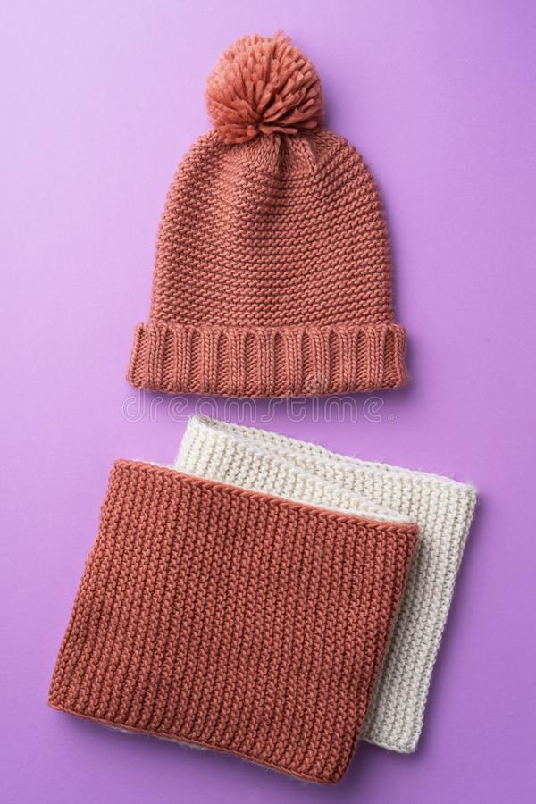 Knit winter hat. And scarf over purple background stock image