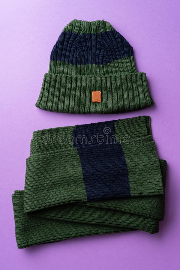 Knit winter hat. And scarf over purple background stock photo