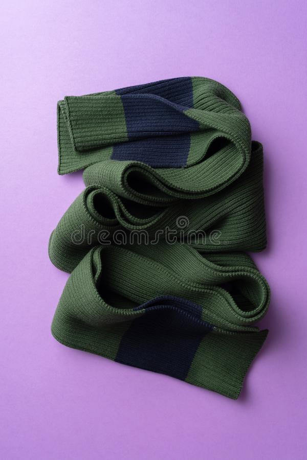 Knit winter scarf. Over purple background royalty free stock image