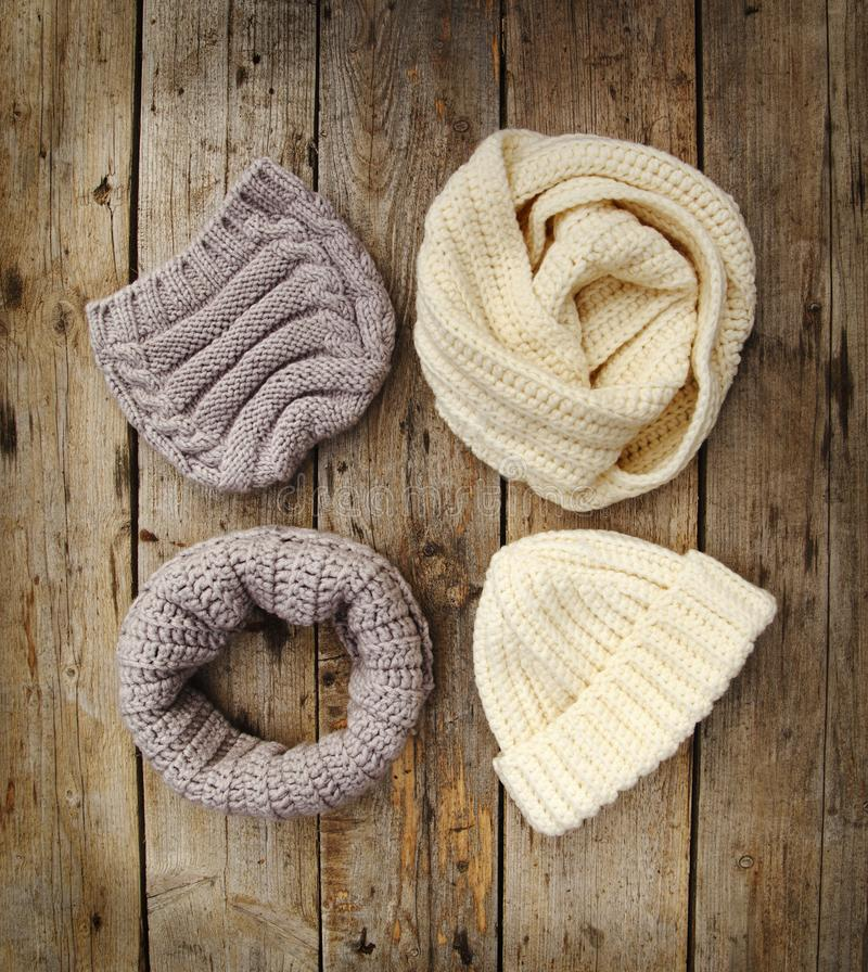 Knit Wool Hats ans Scarfs on wooden background. royalty free stock photo
