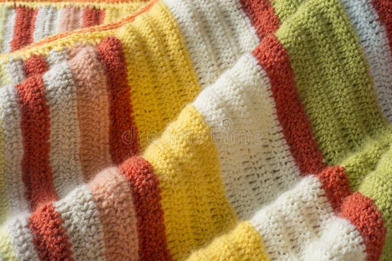 Knitt blanket. Bright warm colored orange and yellow yarn crochet stock photos