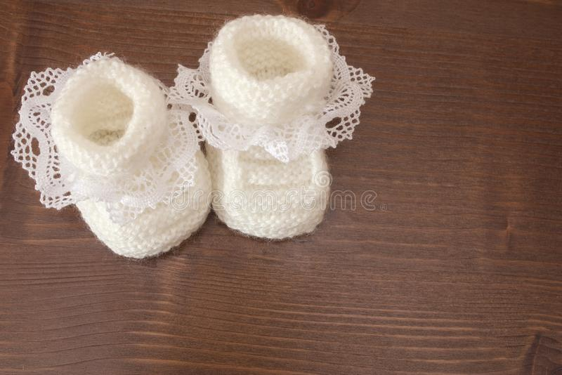 Knitted baby slippers. Are white with a lace on a wooden table royalty free stock photos