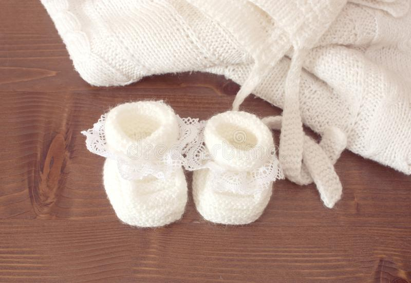 Knitted baby slippers. Are white with a lace on a wooden table stock photos
