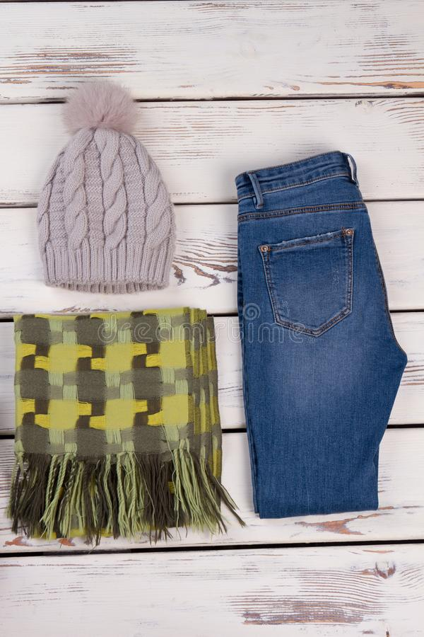 Women`s garments for winter season. Knitted beanie with pom pom, green scarf and typical blue jeans. Women`s garments for winter season stock photo
