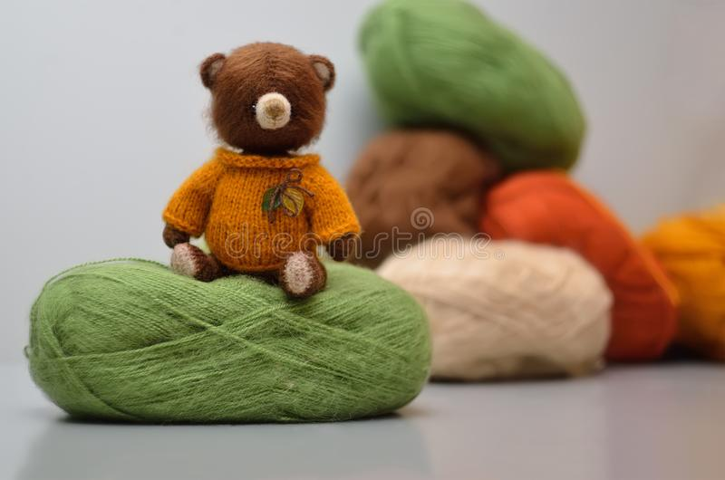 Knitted bear in a yellow sweater in vintage style, with tangles stock image
