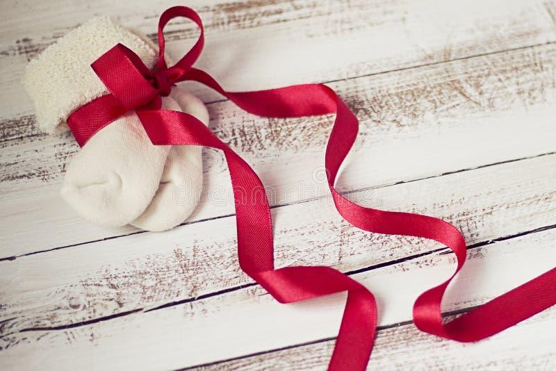 Knitted behandla som ett barn sockor med den röda pilbågen på en träbakgrund arkivbild