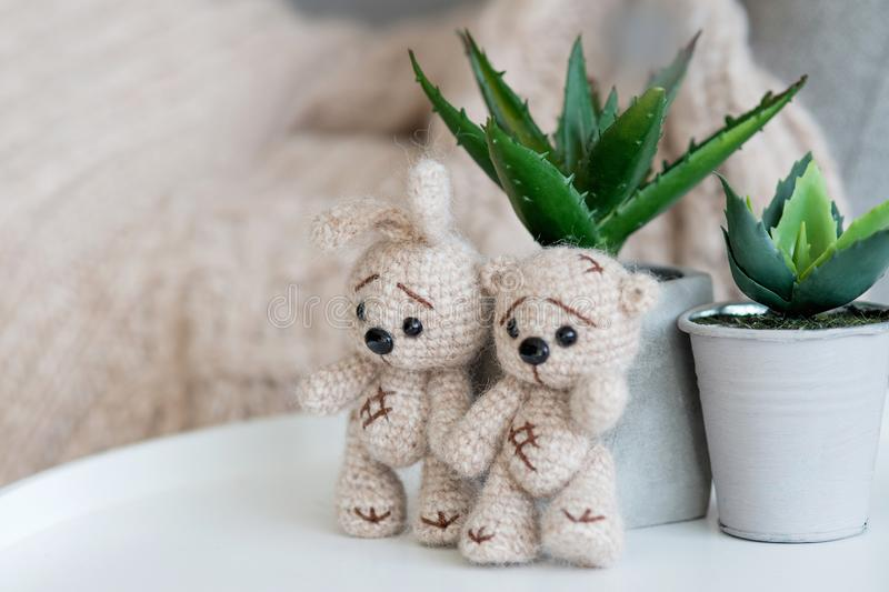 A knitted beige bunny and bear stands next to indoor plants. Behind behind is a sofa on which the plaid handmade is of the same color stock image