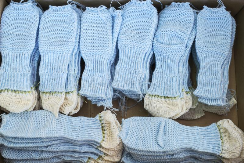 Knitted socks workpieces at knitting shop. Knitted blue ready socks workpieces at a knitting shop view stock photo