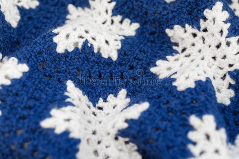 Knitted blue and white ornament with snowflakes stock images