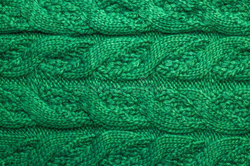 A knitted braids of green threads. A wool sweater ornament. Yarn with knitting. Texture of woolen scarf. Abstract textile backgrou stock image