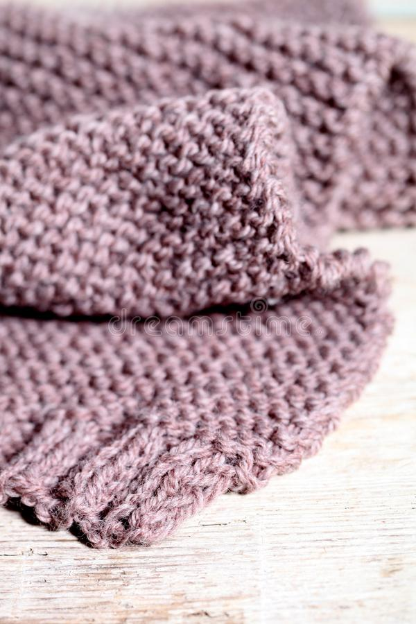 Knitted brown scarf. Knitted brown scarf closeup on wooden background royalty free stock image