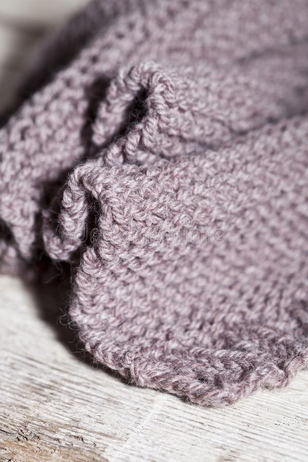 Knitted brown scarf. Closeup on wooden background stock photo