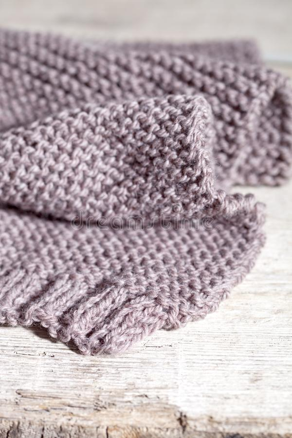 Knitted brown scarf. Closeup on wooden background royalty free stock image