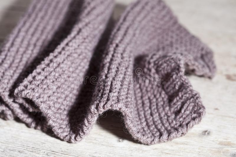 Knitted brown scarf. On wooden background royalty free stock photos