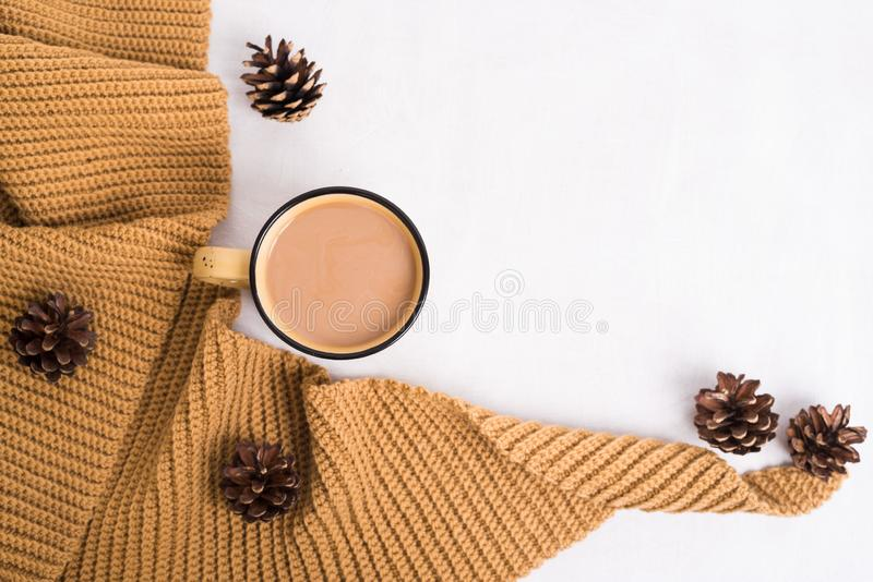 Knitted shawl, cup of coffee and cones on white background royalty free stock photography