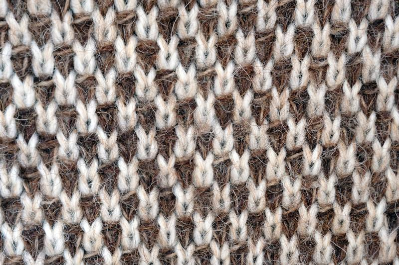 A knitted canvas of woolen threads. Brown and white threads knitting sweaters. Background of woolen fabric stock images