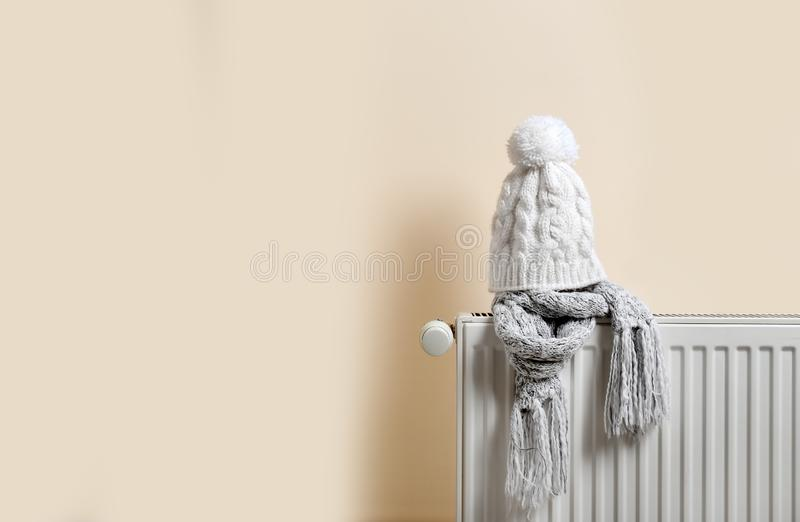 Knitted cap and scarf on heating radiator. Indoors stock photography