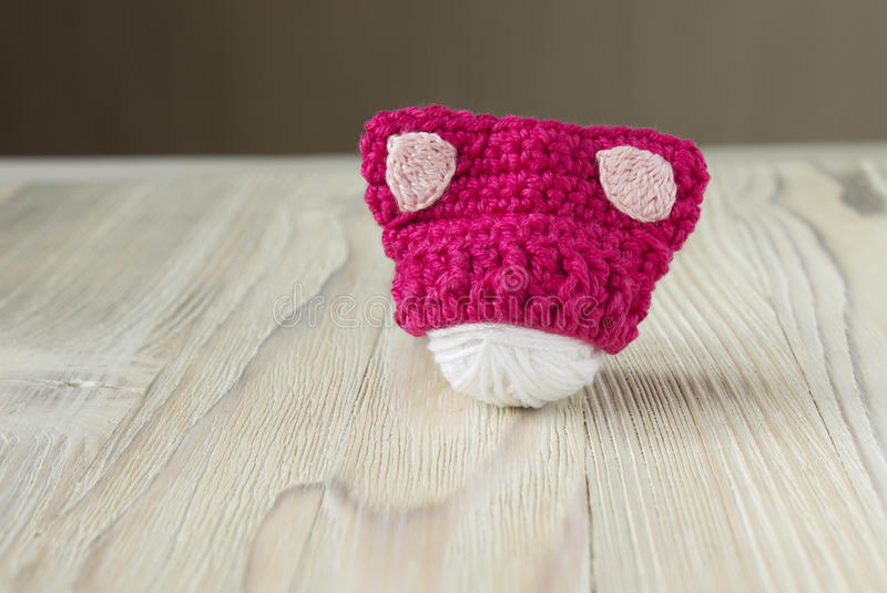 Knitted crochet small pink hat. Women`s hat for feminists march protest. Creative craft work stock image