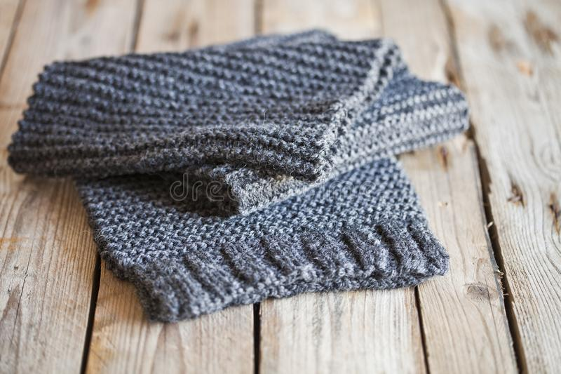 Knitted dark grey scarf. On wooden background stock images