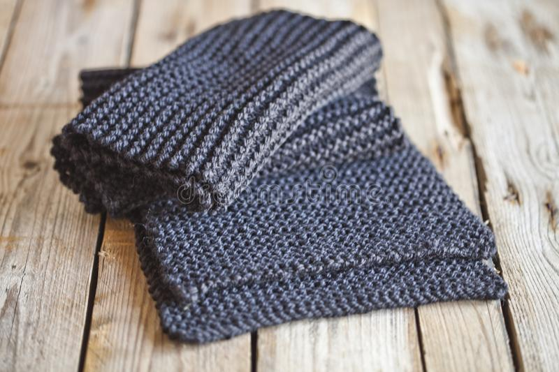 Knitted dark grey scarf. On wooden background stock photos