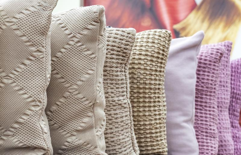 Knitted decorative pillows in different colors on the shop counter stock image