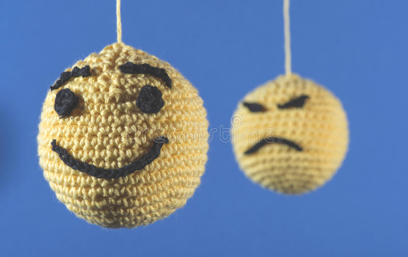 Knitted emoticons. Knitted yellow emoticons on blue background stock images