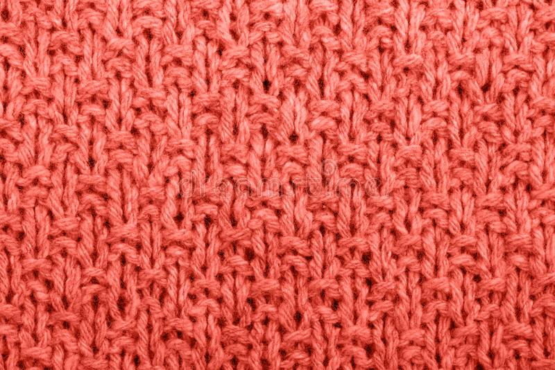Knitted fabric texture living coral color. stock image