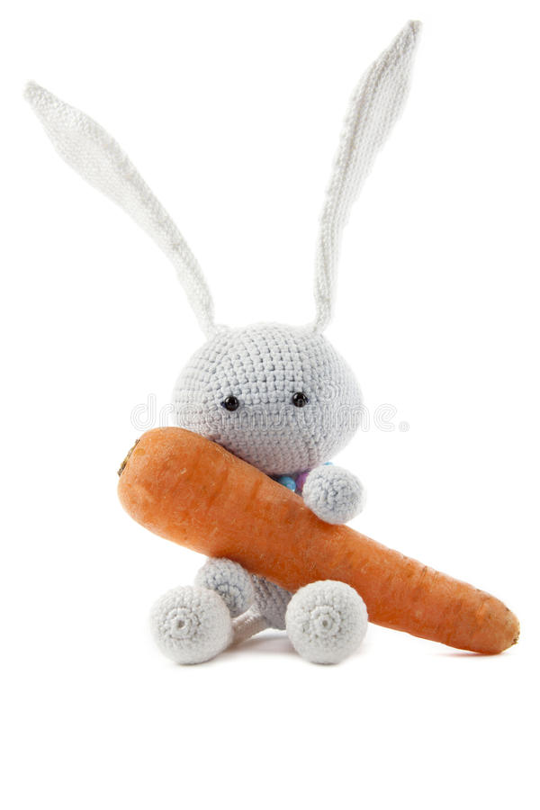 Knitted gray rabbit with carrot royalty free stock photos